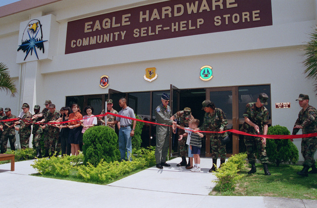 The ribbon cutting ceremony marks the grand opening of Eagle Hardware, a new concept in self-help in the Air Force at Kadena Air Base. On May 22, 1998, Brigadier General John R. Baker, Commander 18th Wing, CHIEF MASTER Sergeant Robert Stivers, SENIOR Enlisted Advisor, and members of the 18th Civil Engineering Squadron, with a little help officially open the store