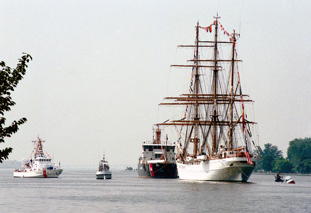 A port bow view of the US Coast Guard (USCG) BARQUE EAGLE (WIX 327) standing offshore near Fort McNair, Washington, District of Columbia (DC), during a Change-Of-Command Ceremony. The USCG KEEPER CLASS: Buoy Tender, USS IDA LEWIS (WLM 551), stands of the Eagles bow. An unidentified USCG ISLAND CLASS: Patrol Craft is underway, extreme left