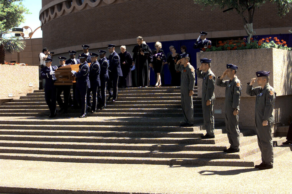 The US Air Force Honor Guard carries the casket of the late Senator and former US Air Force Major General Barry M. Goldwater out of Arizona State Universities' Gammage Auditorium, Tempe, AZ, after the memorial service on 3 June 1998, while pilots representing each squadron from the 56th Fighter Wing, Luke Air Force Base, AZ, salute the departing funeral party