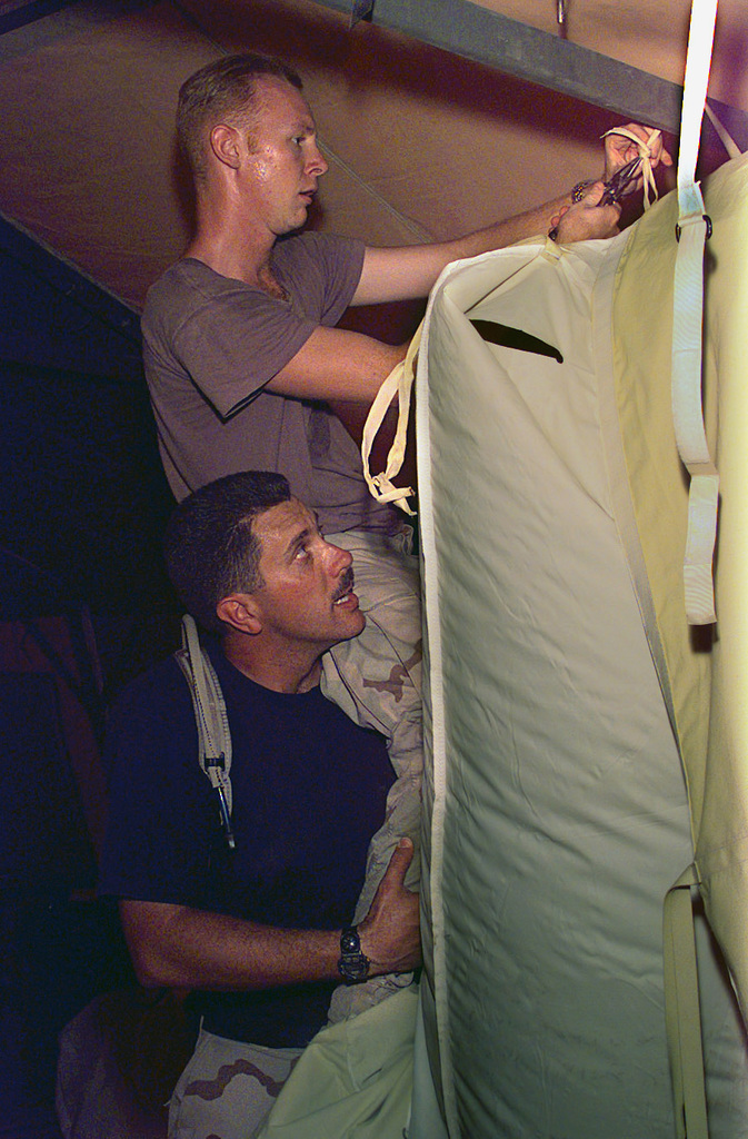US Air Force (USAF) AIRMAN (AMN) Steven Real, Medical Administration Apprentice, gets a boost up from Major (MAJ) Mike Edward, a 4406th Support Group (SG) Air Transportable Hospital (ATH) administrator, as they dismantle tents at Ahmed Al Jaber Air Base, Kuwait, in support of Operation SOUTHERN WATCH 1998