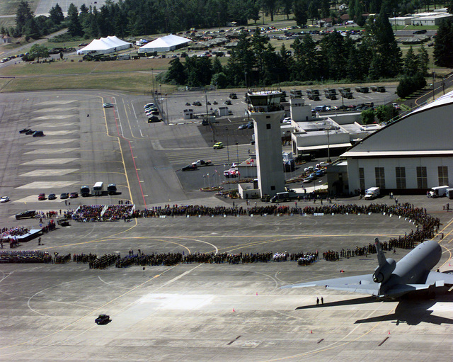 US and international Rodeo 98 Teams stand in formation, while civilian guests and dignitaries sit in moveable bleachers, in front of Hangar 4 for the opening ceremony that kicks off the week-long US Air Force (USAF) Air Mobility Command (AMC) sponsored Rodeo 98 at McChord Air Force Base (AFB), Washington (WA)