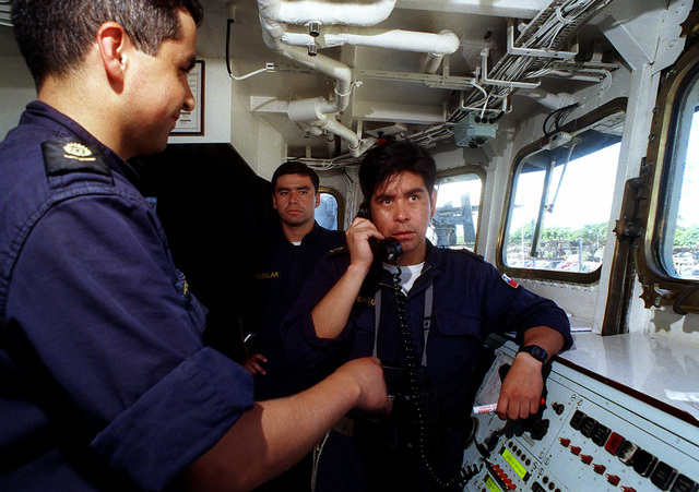 Aboard the bridge of the Chilean frigate CNS CONDELL (FFH 6), PETTY Officer Bienvento (right) communicates with engine room personnel during steam plant evolutions prior to leaving Bravo Pier during the exercise RIMPAC 98