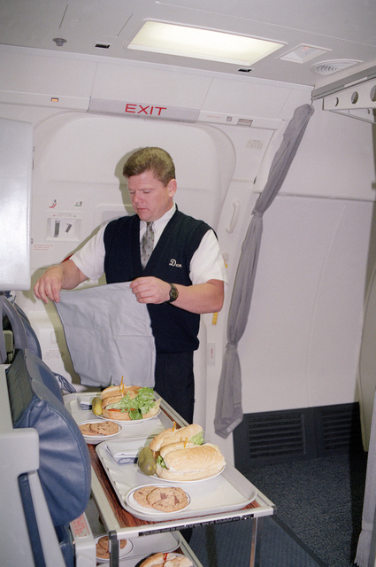 "MASTER Sergeant Dan Casey prepares lunch for personnel headed to Air Mobility Command (AMC) Headquarters on the C-32A, YOTEF (Year of the Enlisted Force) Incentive flight. In May 1997 Air Mobility Command's active duty, guard and reserve leadership designated fiscal 1998 the ""Year of the Enlisted Force."""
