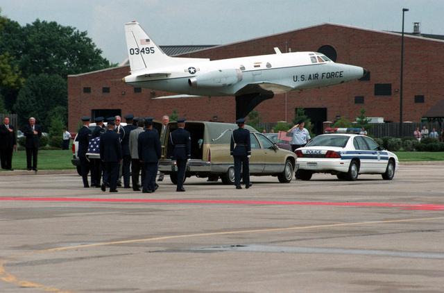 Members of the USAF Honor Guard escort a Team of Pallbearers as they carry the remains of USAF Lieutenant Michael Blassie to a waiting hearse, on the flight line at Scott AFB, Illinois. The remains of Lieutenant Blassie are being returned to his family after lying unidentified for fourteen years in the Tomb of the Unknowns. A mock-up of a USAF T-39 Saberliner aircraft can be seen behind the hearse