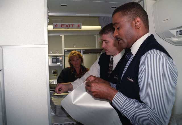 "STAFF Sergeant (SSGT) Irwin Dennis, USAF, (left), SSGT Stephen Johnson, USAF (center), and Technical Sergeant Yasher, USAF, prepare lunch for YOTEF incentive flight personnel headed to Air Mobility Command (AMC) Headquarters aboard the new C-32A. In May 1997 Air Mobility Command's active duty, guard and reserve leadership designated fiscal 1998 the ""Year of the Enlisted Force."""