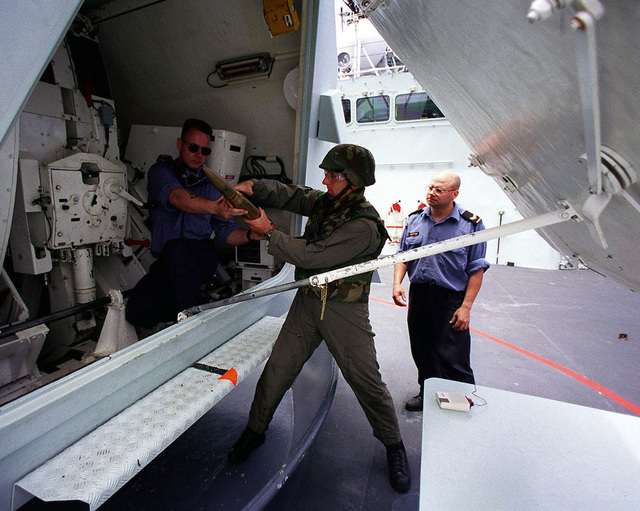 Leading SEAMAN Ken Sawyer (left), a weapons technician aboard the Canadian frigate HMCS REGINA, hands a shell from a jammed 57mm gun mount to PO1 Shelby Cornelius (center), Explosive Ordnance Disposal Mobile Unit Two from Whidbey Island, Washington, during the exercise RIMPAC 98. Another Canadian sailor looks on as the mount is unjammed