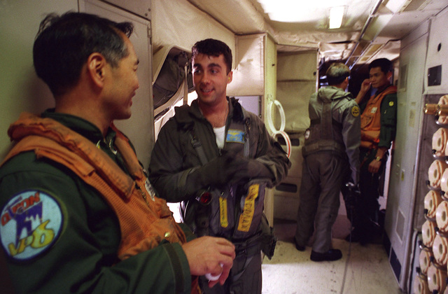 Crewman AD2 (NAC) Anthony Corcoran (second from left) and AE2 (NAC) Richard Parezrosa (second from right) from Patrol Squardron 4 (VP-4) explain emergency procedures to Japanese Maritime Self Defense Force (JMSDF) Detachment 33 aircrewmen Takeshi Okamato (left) and Fumio Sato (right) during a crosstraining mission of Japan and U.S. Bilateral Force as part of the exercise Rimpac 98
