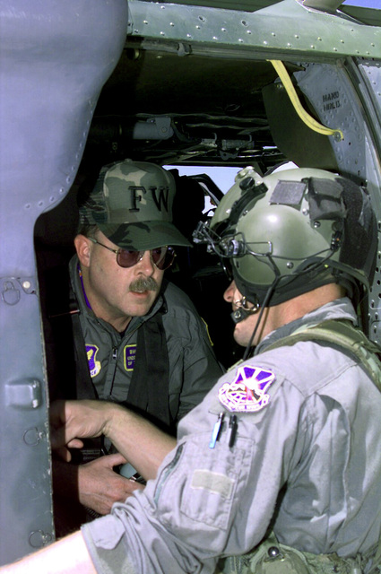 Acting Secretary of the Air Force F. Whitten Peters (Left) visited Luke Air Force Base (AFB), Arizona for a better understanding of the issues involved in the renewal of the Barry M. Goldwater range. F. Whitten Peters receives preflight instruction from a member of the 305th Rescue Squadron, Davis-Monthan AFB, Arizona, prior to flying to the Goldwater range for a tour