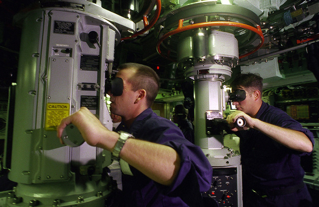Two crewmembers aboard the nuclear powered attack submarine USS PASADENA (SSN 752) sweep the horizon through periscopes as the sub prepares to surface during exercise RIMPAC 98