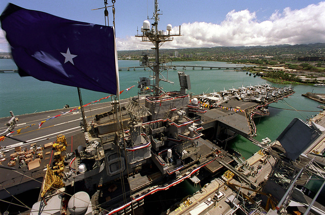 The soon to be decommissioned aircraft carrier USS INDEPENDENCE (CV 62), with bunting and flags, is shown as the flag of RDML Timothy J. Keating, Commander, Carrier Group Five, flies high above the aircraft carrier USS KITTY HAWK (CV-63) which is assuming her new duties as American's only permanently forward-deployed aircraft carrier