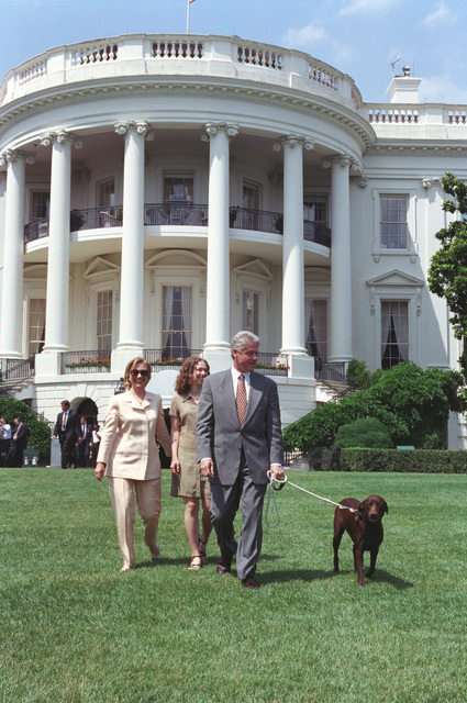 Photograph of President William Jefferson Clinton, First Lady Hillary Rodham Clinton, Chelsea Clinton, and Buddy the Dog Walking on the South Lawn