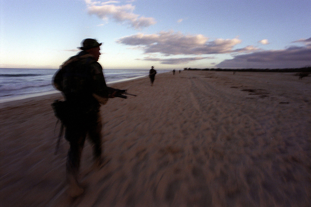 US Marines of the 13th Marine Expeditionary Unit, Camp Pendleton, California, armed with M-16 rifles, from Boat Co., Foxtrot 21, Camp Pendleton, California clear the beach for an amphibious assault during exercise RIMPAC '98