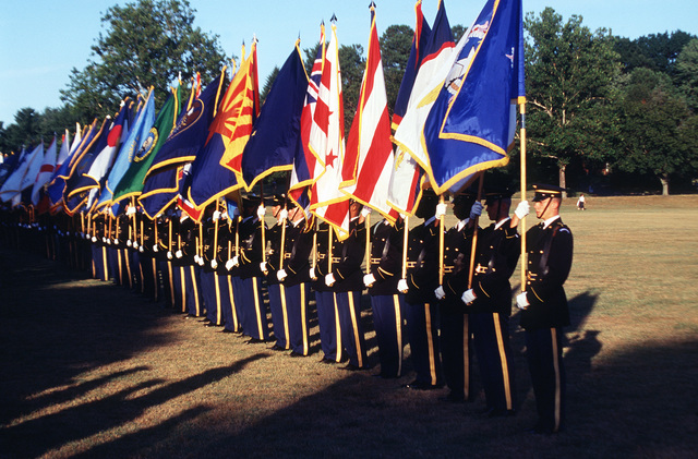 Members of the 3rd Infantry (Old Guard) holding state and U.S. territorial flags prepare to march during the Twilight Tattoo ceremony