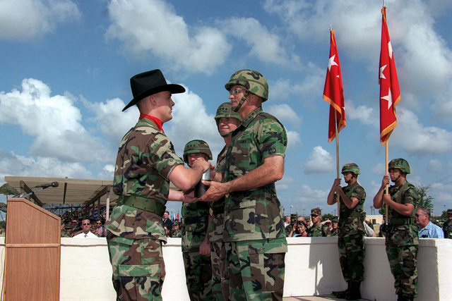 A member of III Corps (wearing black cowboy hat) presents the outgoing commander, LGEN Thomas A. Schwartz with a shell casing during the change of command ceremony. LGEN Leon J. LaPorte (second from left), the new III Corps commander, GEN David Bramlett (behind LGEN Schwartz), Commander, U.S. Army Forces Command look on