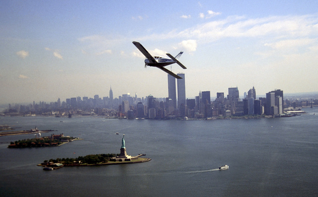 An Aero-Club Piper Arrow aircraft flies up New York Harbor towards the Statue of Liberty and the World Trade Centers and during sightseeing trip to New York City