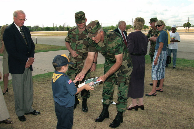 LGEN Thomas A. Schwartz, the outgoing commander of III Corps, signs a photograph for a Cub Scout after the change of command ceremony