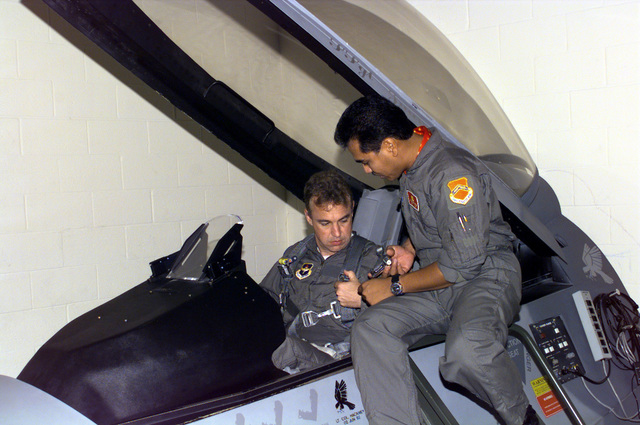 A US Air Force member (Right) of the 56th Fighter Wing's Egress Team, Luke Air Force Base, Arizona, assists US Congressman Matt Salmon, Representative of Arizona's 1ST District, in a simulator as he gets the proper training before his upcoming F-16 Falcon flight