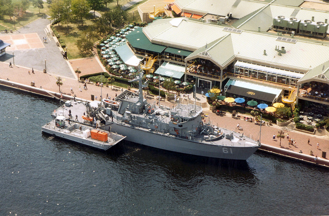High angle view showing the US Navy (USN) OSPREY CLASS (MINEHUNTER COASTAL), USS RAVEN (MHC 61), being assisted by a US Navy Reserve (USNR), MECHANISED LANDING CRAFT: LCM 8 TYPE craft, assigned to Assault Craft Unit Two -27(ACU2-27), as it conducts mooring operations at Pratt Street Pier #4 in the inner harbor, Baltimore, Maryland (MD)