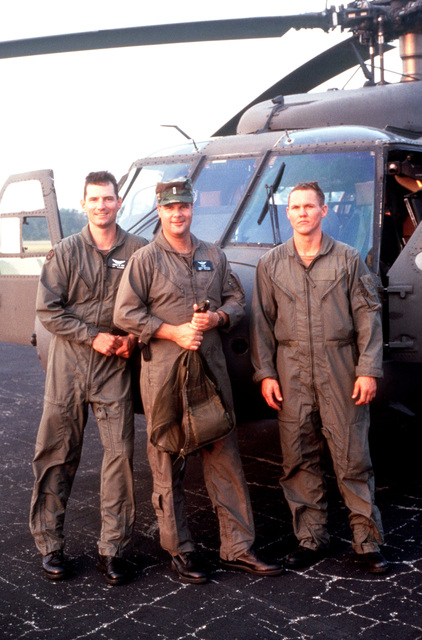 Three crewmen of a North Carolina National Guard UH-60 Black Hawk helicopter pose for a photograph in front of their aircraft at the Wilmington Airport