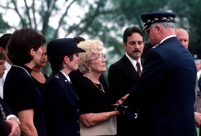 Gene Blassie (2nd from left) receives a folded American flag from USAF CHIEF of STAFF Michel Ryan during First Lieutenant Michael Blassie's funeral service at Jefferson Barracks National Cemetery, Missouri. 1LT Blassie was shot down and killed in South Vietnam on May 11th, 1972. A mix up with dog tags and body identification led the remains listed as Unknown and buried in the tomb of the Unknown Soldier at Arlington National Cemetery (Not shown). Using DNA testing on May 14th, 1998, the remains were identified as those of 1LT Blassie and services were held in his honor. This image is seen in the September 1998 edition of AIRMAN Magazine