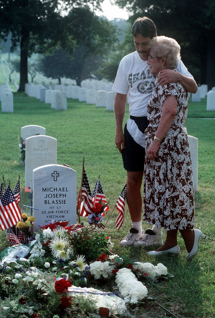 Jean Blassie (Right) and her son George Blassie, brother of USAF First Lieutenant Michael Blassie, gather at his gravesite in Jefferson Barracks National Cemetery in St. Louis, Missouri. 1LT Blassie was shot down and killed in South Vietnam on May 11th, 1972. A mix up with dog tags and body identification led the remains listed as Unknown and buried in the tomb of the Unknown Soldier at Arlington National Cemetery (Not shown). Using DNA testing on May 14th, 1998, the remains were indentified as those of 1LT Blassie and services were held in his honor. This image is seen in the September 1998 edition of AIRMAN Magazine