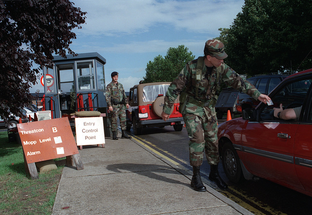 Suffolk County, England. USAF AIRMAN First Class (A1C) Fred Winchell a Security Forces augmentee, assigned to the 100th Communication Squadron Royal Air Force (RAF) Mildenhall check identification and vehicle registration at a temporary entry control point during Threat Condition Bravo as A1C Ray Hynes, from the 100th Security Forces Squadron looks on. Security has been increased in response to terrorist attacks in Africa and the United States Retaliation to those attacks