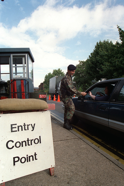Suffolk County, England. USAF AIRMAN First Class (A1C) Ray Hynes, from the 100th Security Forces Squadron, Royal Air Force (RAF) Mildenhall check identification and vehicle registration at a temporary entry control point during Threat Condition Bravo. Security has been increased in response to terrorist attacks in Africa and the United States Retaliation to those attacks