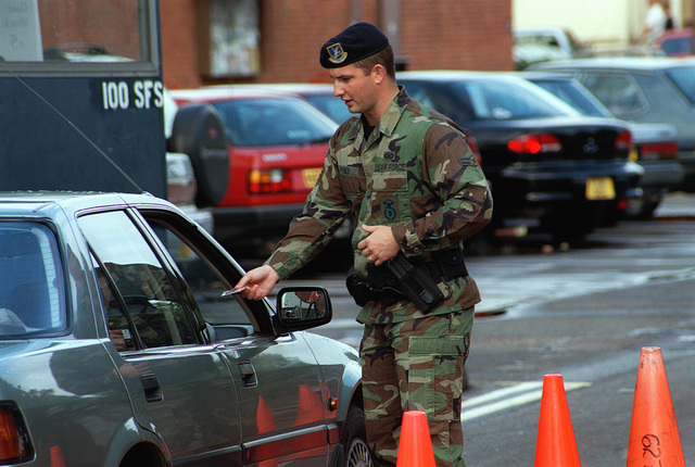 Suffolk County, England. USAF AIRMAN First Class (A1C) Ray Hynes, from the 100th Security Forces Squadron, Royal Air Force (RAF) Mildenhall checks identification and vehicle registration at a temporary entry control point during Threat Condition Bravo. Security has been increased in response to terrorist attacks in Africa and the United States Retaliation to those attacks