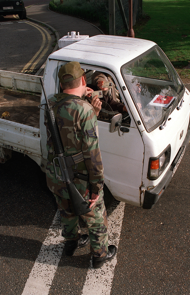 Suffolk County, England. USAF STAFF Sergeant Danny Albert, a Security Forces augmentee from the 100th Logistics Squadron, Royal Air Force (RAF) Mildenhall checks the identification of visitors in commercial vehicles entering Gate 1 at RAF Mildenhall during Threat Condition Bravo. STAFF Sergeant Albert is armed with a 5.56 mm M16A2 assault rifle. Security has been increased in response to terrorist attacks in Africa and the United States Retaliation to those attacks