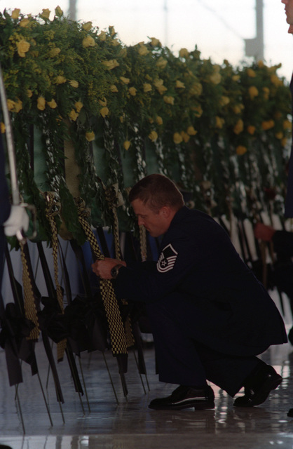 MASTER Sergeant Hank Wiswell from the 66th Rescue Squadron pins a memento on the scarf during the memorial ceremony for the twelve airmen killed in the helicopter accident. The airmen died when two HH-60G Pavehawk helicopters crashed 25 miles north of Indian Springs in the Pintwater Mountain Range, at night, during a simulated rescue mission of a survivor on the ground