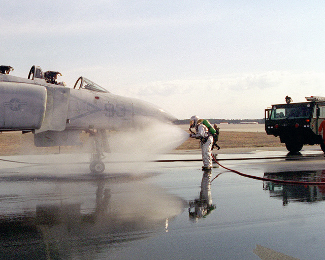 A US Marine from crash fire rescue, hoses down an F-4 Phanton assisted by a P-19 fire truck, during an emergency casualty drill. On the flight line of Marine Corps Air Station Cherry Point, North Carolina