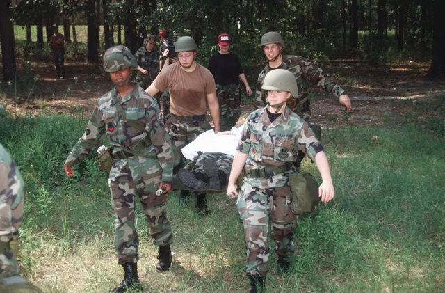 US Air Force Personnel, AIRMAN First Class (A1C) Abernathy, STAFF Sergeant Campbell (front left to right), A1Cs Nixon and Mckean carry an injured soldier to a field hospital for treatment. The 2nd MG is participating in Continuing Medical Readiness Training on the East Reservation of Barksdale Air Force Base, Louisiana, from 21 September through 25 September 1998. Medical personnel are involved in unrehearsed medical situations during wartime conditions