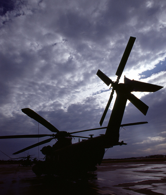 A stern portside view of an USAF MH-53J Enhanced Pave Low III Helicopter parked on the runway at Hurlburt Field, Florida. The setting sun and clouds silhouette the image