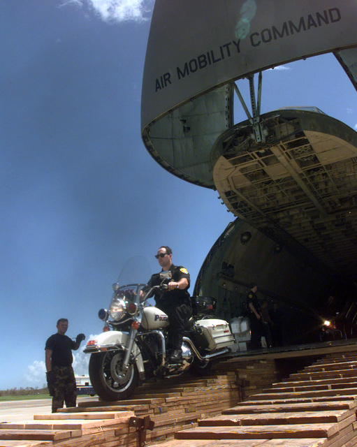 A US Federal Protection Service member rides his police motocycle off a C-5 Galaxy cargo aircraft at Naval Station Roosevelt Roads. The C-5 from the 436th Air Mobility Wing is one of many Air Mobility Command (AMC) aircraft currently tasked to airlift equipment and supplies to Puerto Rico and neighboring Caribbean Islands struck by Hurricane George