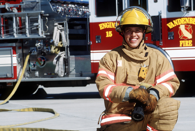 "Straight on medium close-up of USAF AIRMAN Mike Arzabal in full firefighter gear as he kneels down next to a Vandenberg Air Force Base fire truck. AMN Arzabal, a Fire Protection Apprentice, is assigned to the 30th Civil Engineering Squadron at Vandenberg AFB, California. About being a fire fighter, he states, ""Aside from the adrenaline rush, I love the fact that I can help people out of possible fatal situations."""