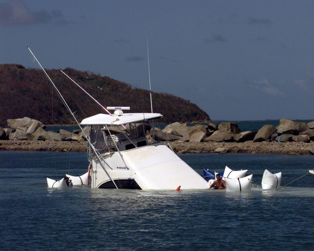 A local boat owner can only sit in his half-submerged boat as it is towed to dry dock at Marina del Rey in Fajadro, Puerto Rico. Hurricane George winds caused devastating damage to homes and property though out Puerto Rico and other neighboring Caribbean Islands