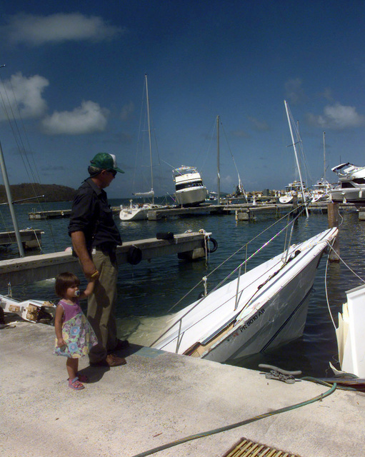 A local boat owner looks at his neighbor's sunken boat that didn't fair well after Hurricane George ripped though the city of Fajardo, Puerto Rico. Boats at Marina del Rey were literally lifted from their dock slips during Hurricane George's rampage last Monday