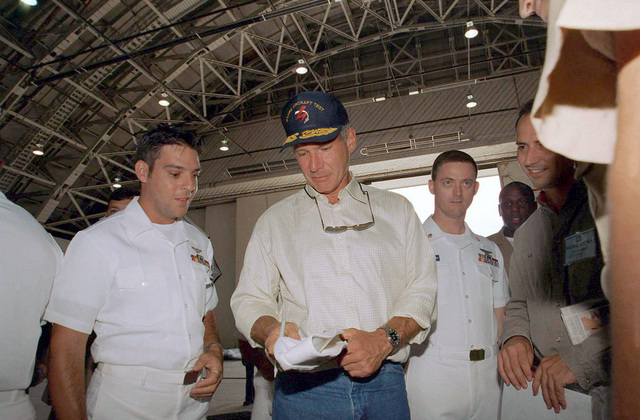 Harrison Ford pauses to sign autographs for the sailors of Naval Air Station NAS Patuxent River, Maryland, while on location shooting Random Hearts. Three scenes were filmed in a hangar on NAS Patuxent River and involved many active duty personnel as extras