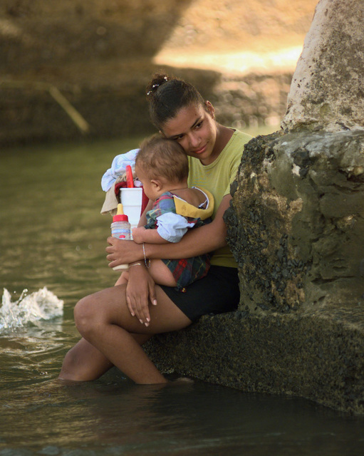 Sitting at the base of the bridge that leads into the small town of Fajardo, Puerto Rico, a young women shares a quite moment with her child after doing her laundry in the town's local river. Because of Hurricane George's destructive effects the town has been without electricity for the past two days. Her and the other residents of Fajardo currently use the river to bathe and wash clothing