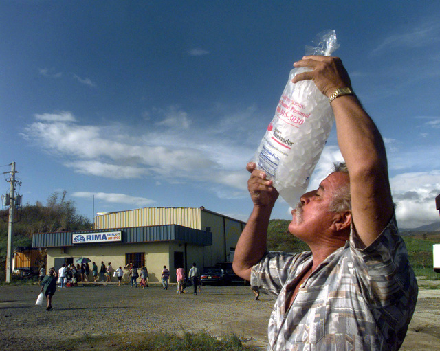 A man enjoys a cold drink of melted ice finding relief from Puerto Rico's scorching heat. He and others have been waiting in line for over two hours some even camp out over night outside the factory gate in order to be first in line to buy ice. The demand for ice is so great that the owner of the factory limits the sale of ice to one bag per person. The Rima ice factory is one of three factories currently working with the US Federal Emergency Management Agency (FEMA) in order to provide ice to the local communities hit by the devastating winds of Hurricane George