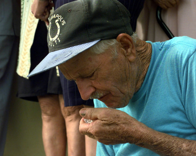 An elderly gentleman enjoys a handfull of ice getting some relief from Puerto Rico's scorching heat. The demand for ice is so great that the owner of the factory limits the sale of ice to one bag per person. The Rima ice factory is one of three in the local area currently working with the US Federal Emergency Management Agency (FEMA) to provide ice to the local communities hit by the devastating winds of Hurricane George