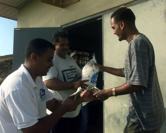 Workers for the Rima ice factory located just north of Fajardo, Puerto Rico sell bags of ice to the local public. The demand for ice is so great that the owner of the factory limits the sale of ice to one bag per person. The Rima ice factory is one of three in the local area currently working with the US Federal Emergency Management Agency (FEMA) to provide ice to the local communities hit by the devastating winds of Hurricane George