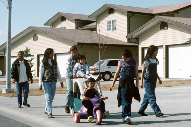 USAF MASTER Sergeant Larry Mingus (Pushing the stroller), with his family and friends, take a stroll in front of Eielson's modern base housing. Newer units feature two-car garages and full basements (basements not shown)