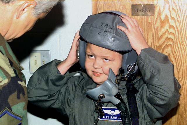 Caleb Barfield, Pilot for a Day, with MASTER Sergeant Tommy Temple. MSGT Temple, Non-Commissioned Officer In Charge, tells Caleb about the helmet he is wearing. The 157th Fighter Squadron, 169th Fighter Group, McEntire Air National Guard Station, Eastover, South Carolina, is host for the Pilot for a Day Program