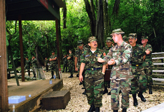 United States Army Sergeant Jeffrey Adams, instructor, A Company, Joint Operations Training Battalion, briefs El Salvadorian Army General Juan Antonio Martinez Varela at a mines and booby trap training area