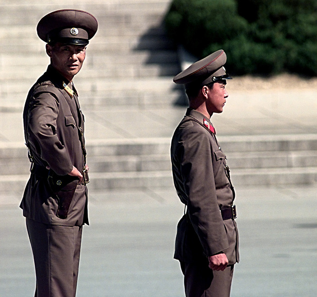North Korean guards stand at their post providing protection for a group of people touring North Korean side of the Demarkation line. The North Korean guards are posted to keep people from defecting from North to South Korea. Both sides have guards posted at the same time and stand face to face on a daily basis
