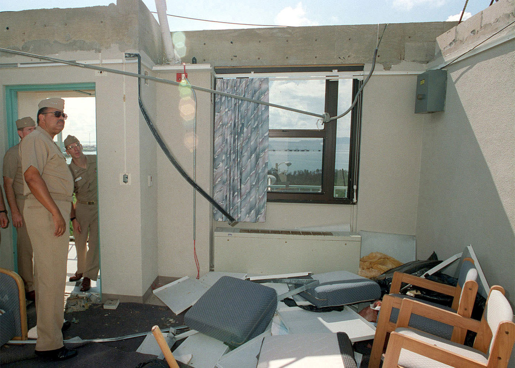 Admiral J. Paul Reason, Commander in CHIEF, Atlantic Fleet, observes a barracks room destruction caused by Hurricane Georges on Naval Station Roosevelt Roads, Puerto Rico