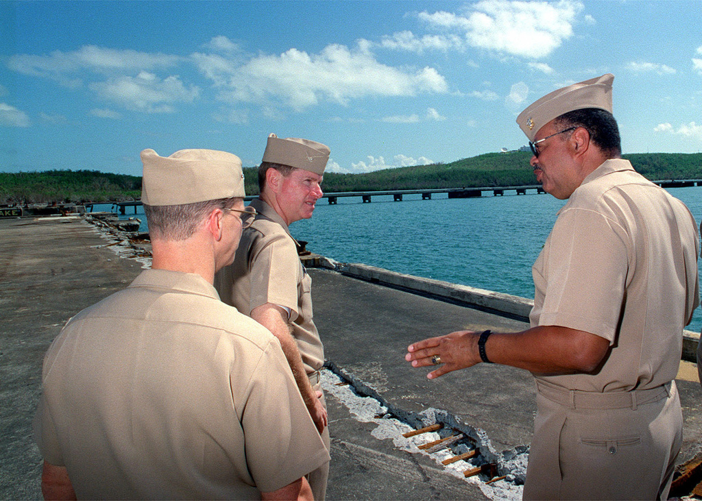 Admiral J. Paul Reason (right), Commander in CHIEF Atlantic Fleet, speaks with James K. Stark, Commanding Officer, Naval Station Roosevelt Roads, Puerto Rico, and Commander Chuck Cassidy (left) concerning damage inflicted to piers during Hurricane Georges