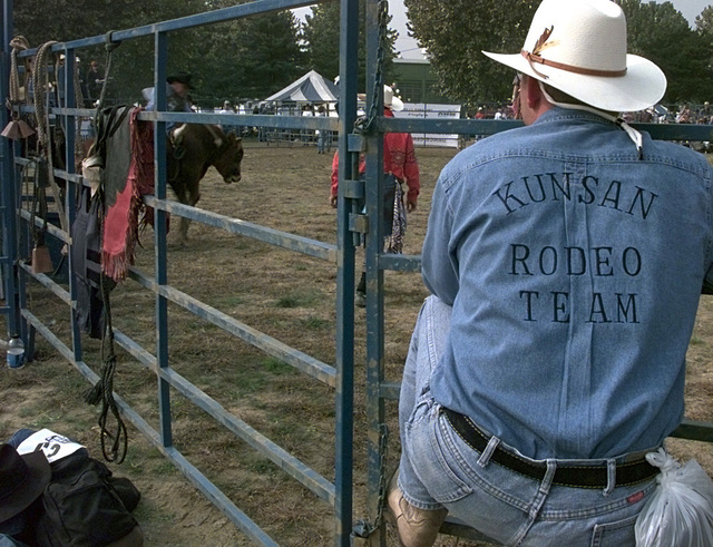 Workers line the fences to watch the bull riding competition at the rodeo. The rodeo workers and participants are part of the Korean/American Cowboy Association (KACA) which was founded in 1996. The KACA is officially recognized by as a private organization by the Morale, Welfare and Recreation of the Army. The KACA is made up of 260 members and continues to grow. The rodeo is part of the Columbus Day community fair at Yongsan Army Post, Korea. The fair included games for children, food, live entertainment along with the rodeo