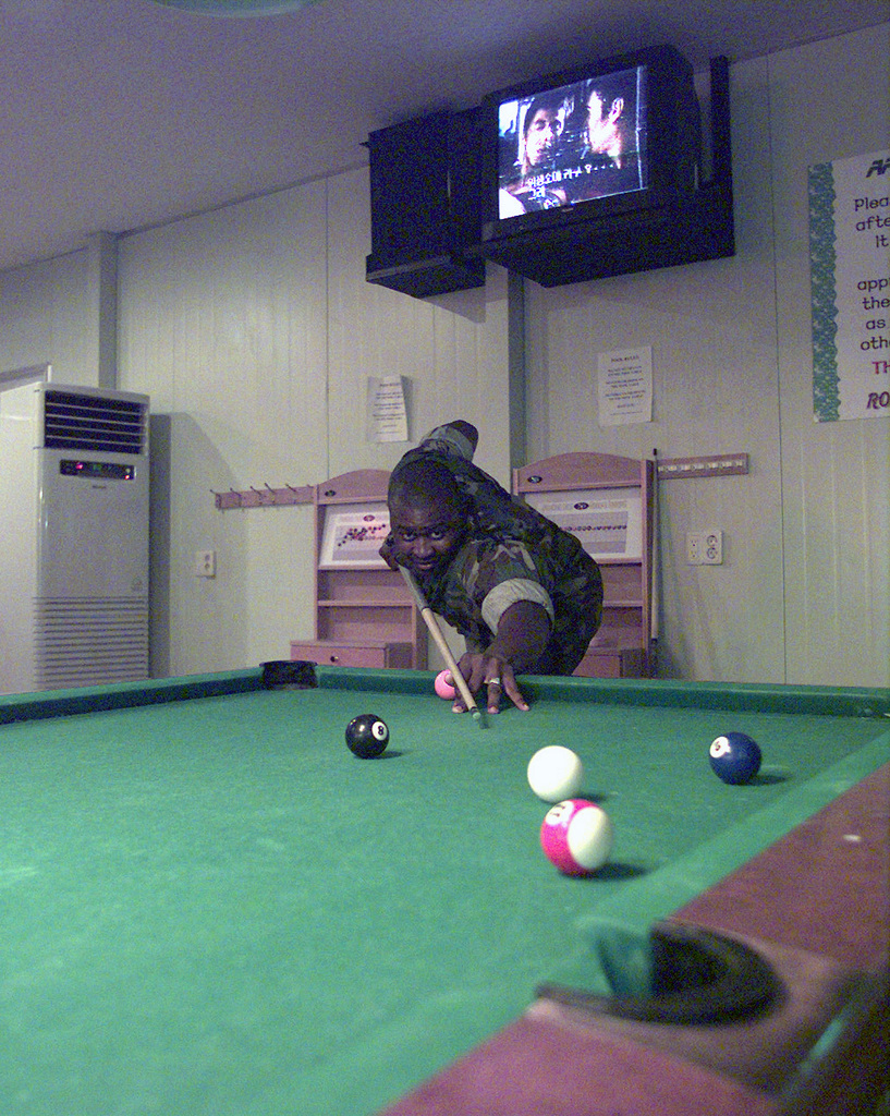 Boatswain's Mate (BM2) Sheon Hunte plays pool during some free time at the ROK Hard Cafe at Marine Expeditionary Camp-Pohang (MEC-P), South Korea. Hunte is from the Navy Cargo Handling in Port Group, Williamsburg, Virginia, and is deployed to MEC-P in support of Exercise FOAL EAGLE '98. FOAL EAGLE is designed to test rear area protection operations and major command, control and communications systems